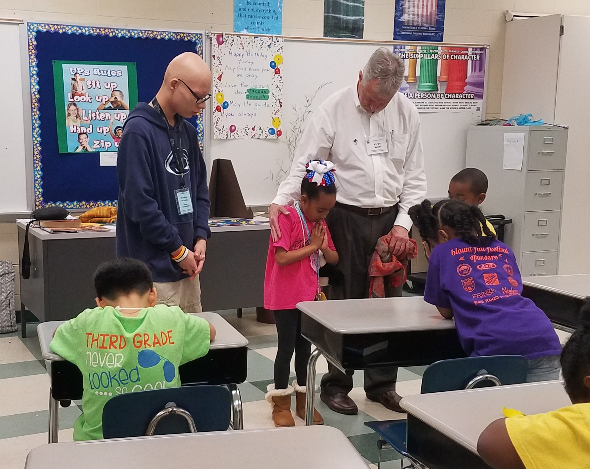 Pastor Kirby Smith helps a student lead prayer at the Blount Elementary  Good News Club® .