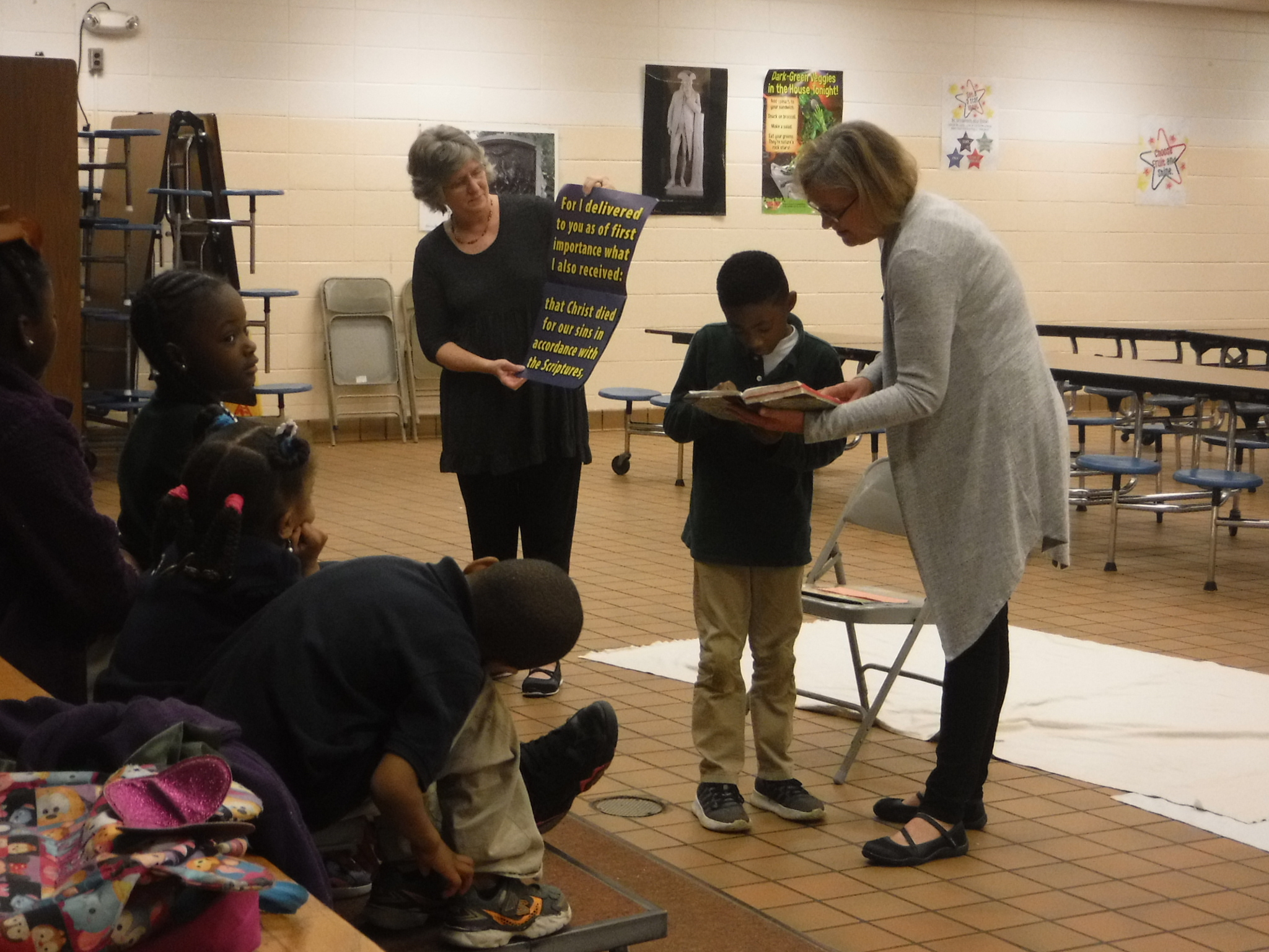Karen Blake and Pam Jernigan of Grace Presbyterian Church teach Ephesians 2:8 and 9 to students at Dozier Elementary  Good News Club® .