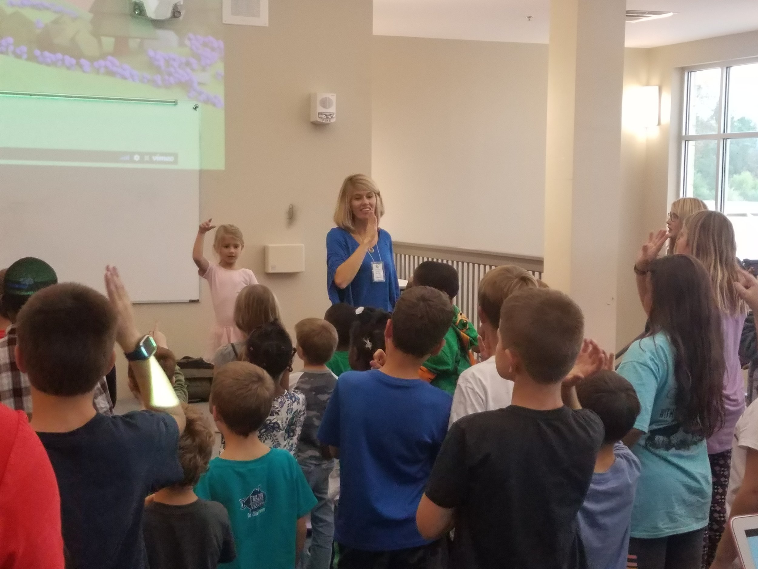 "Volunteer from Church @ Pike Road leads students in the song, ""He is God"", at the Pike Road Elementary  Good News Club® ."