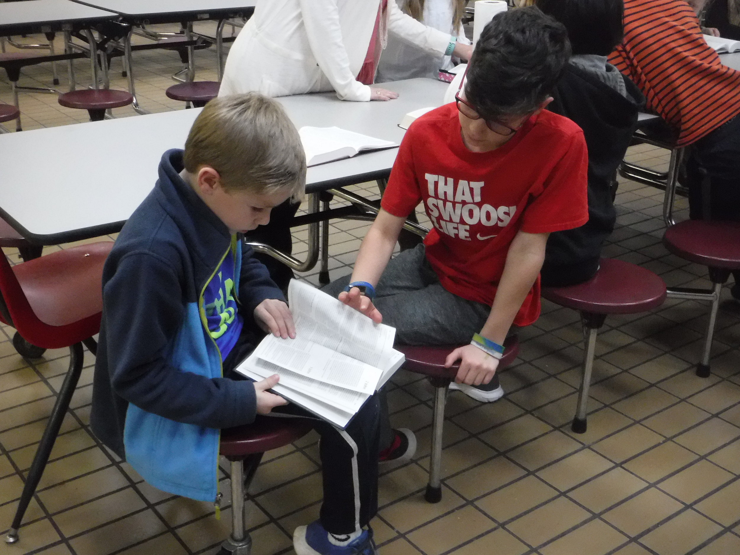 Students help each other find Scripture at Eclectic Elementary  Good News Club® .