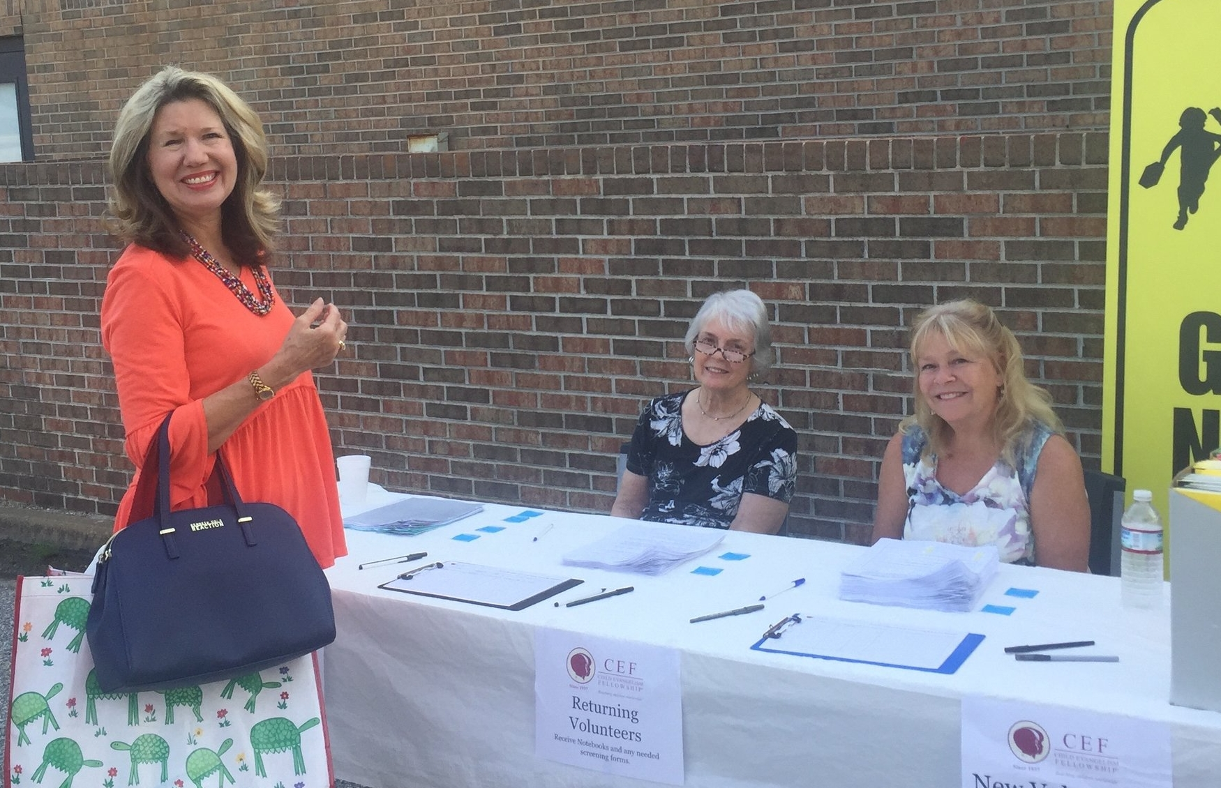 Linda Brown (far left) welcomes and registers volunteers at the annual  Good News Club®  Training.