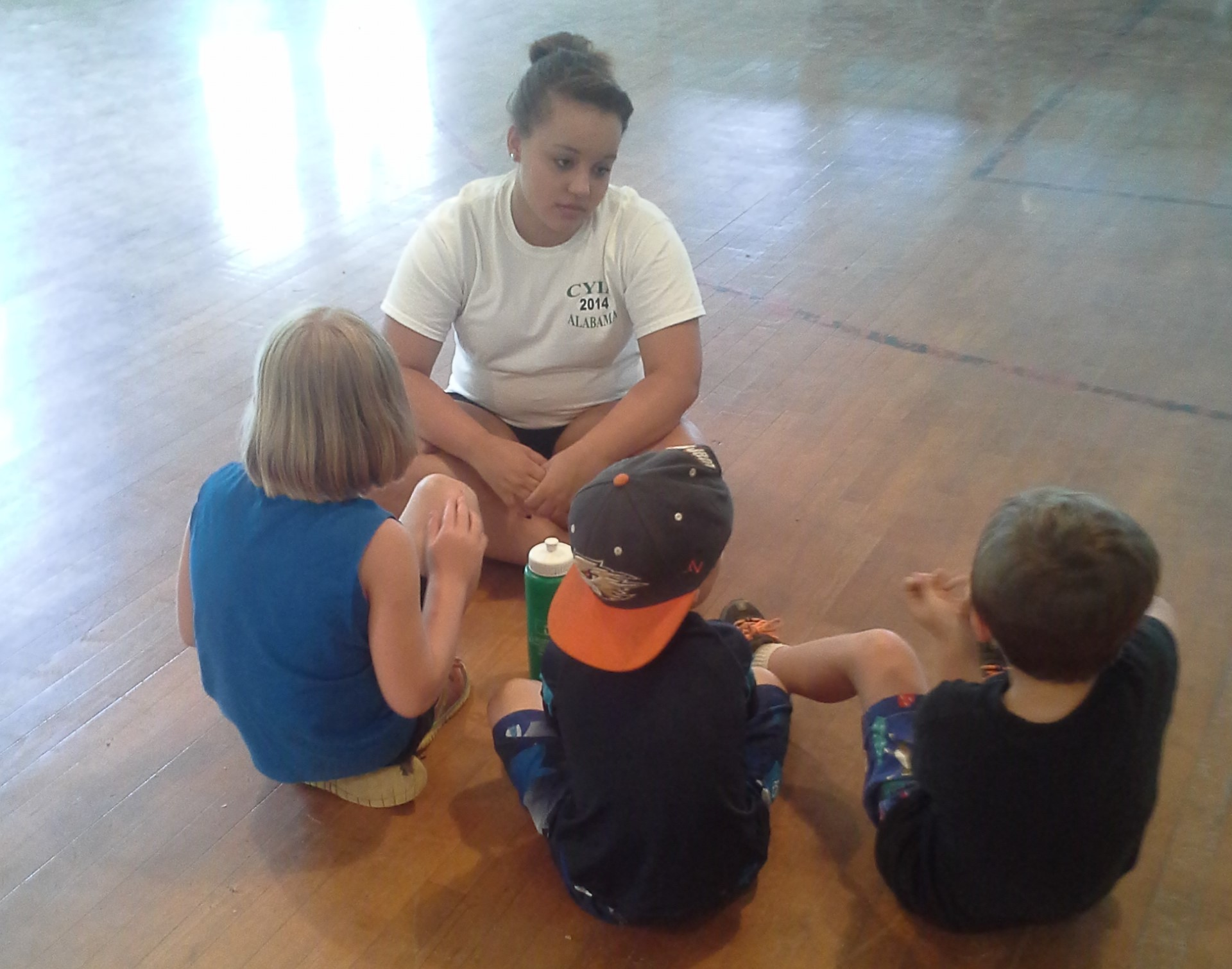 Jade Marcum counsels children after the Bible lesson at a Camp Grandview  5-Day Club®  in Wetumpka, Alabama.