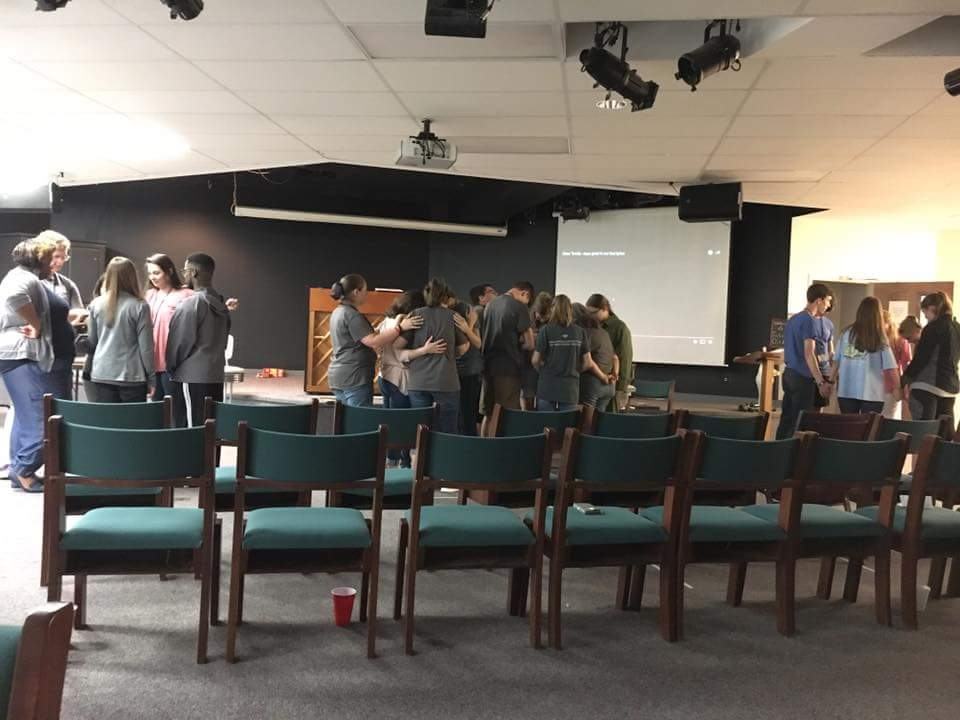 Students at  Christian Youth In Action®  pray over each other during evening worship.
