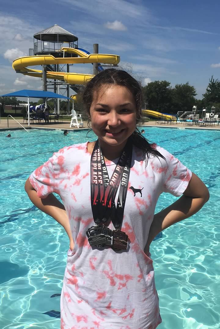 Kaitlyn Garcia-Allen dons her medals after the Dallas Classic Summer Swim League Championships.