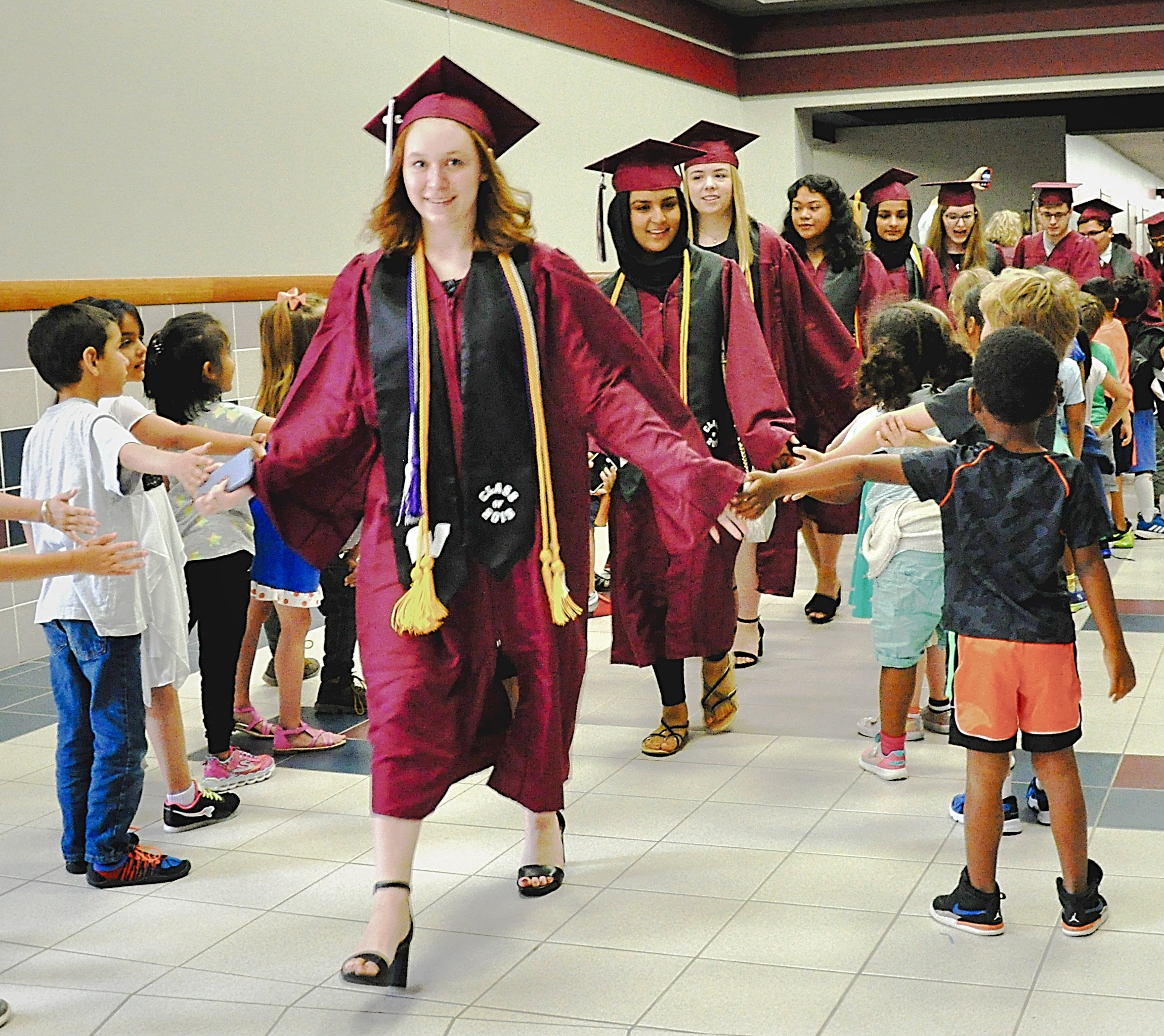 Zoe Goldade walks the halls giving high-fives to students.