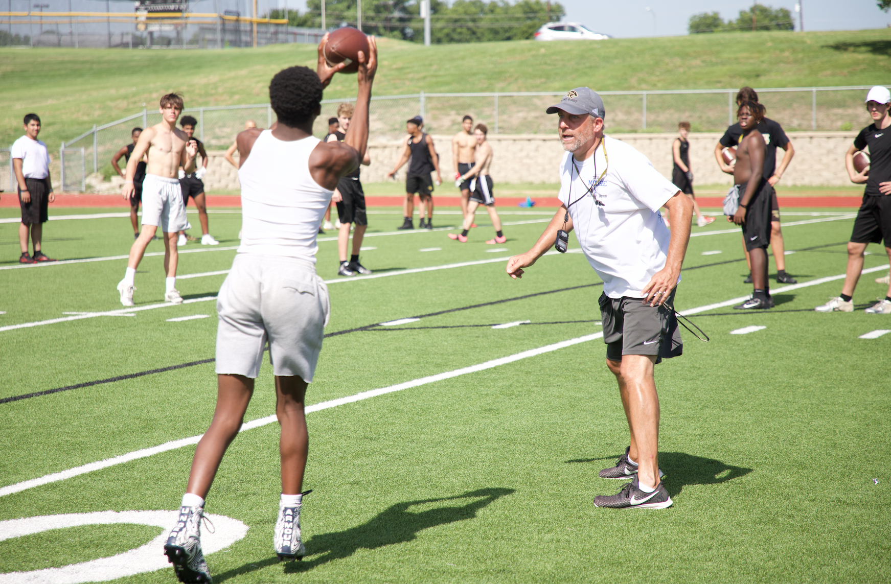 Offensive Coordinator, Brad Bailey, works with receivers on running routes properly..png