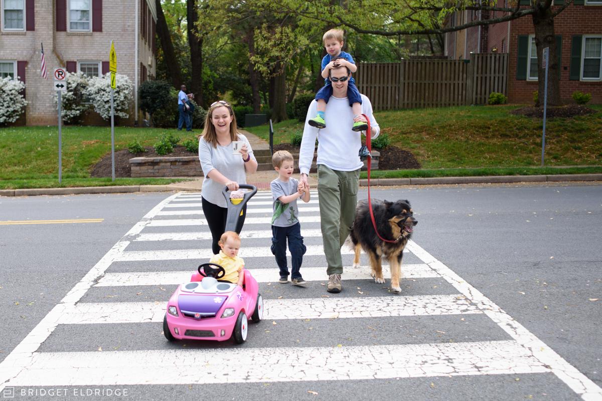 family crosses the street together on a neighborhood walk