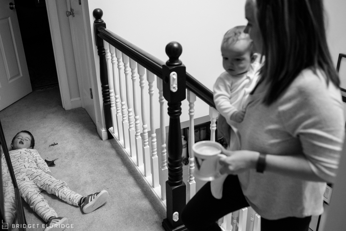 little boy pretends to be sleeping as mom comes upstairs