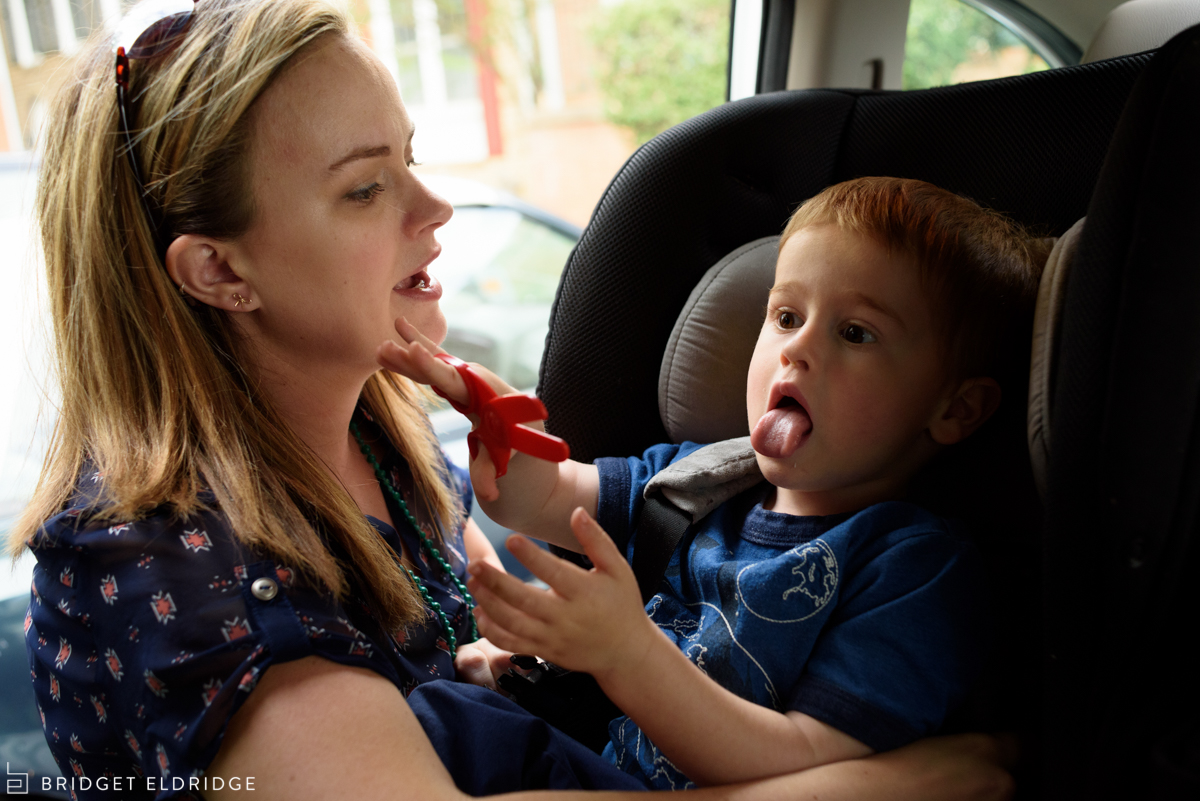 mom buckles son in the car