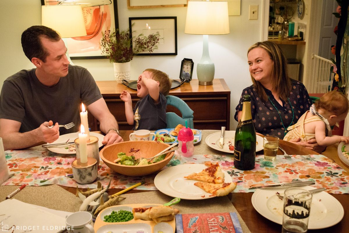 parents enjoy a chaotic dinner with a bottle of champagne