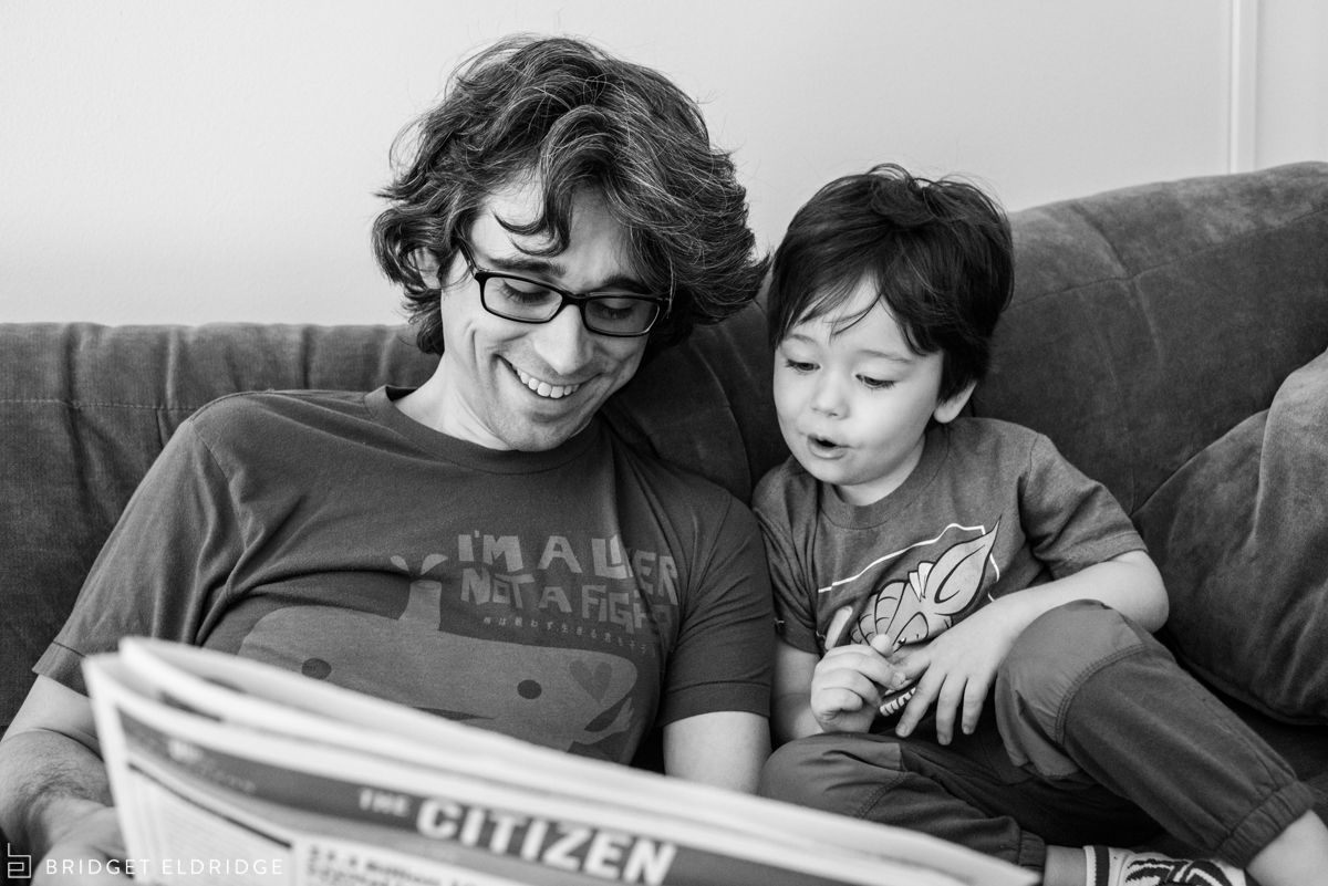 father and son read the paper together