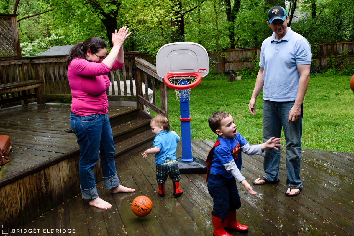 family plays basketball outside in the rain