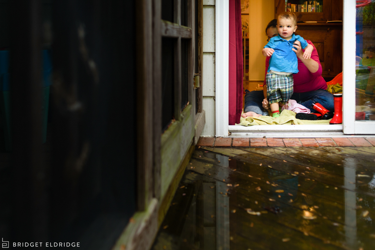 mom takes wet rain boots off her son