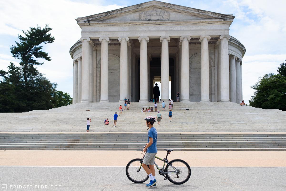 boy walks his bike in front of the jefferson memorial