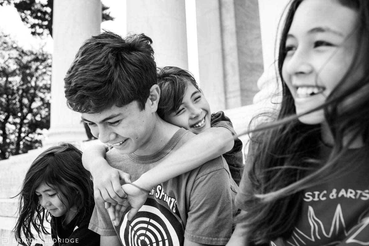siblings hug each other on the steps of the jefferson memorial in washington dc