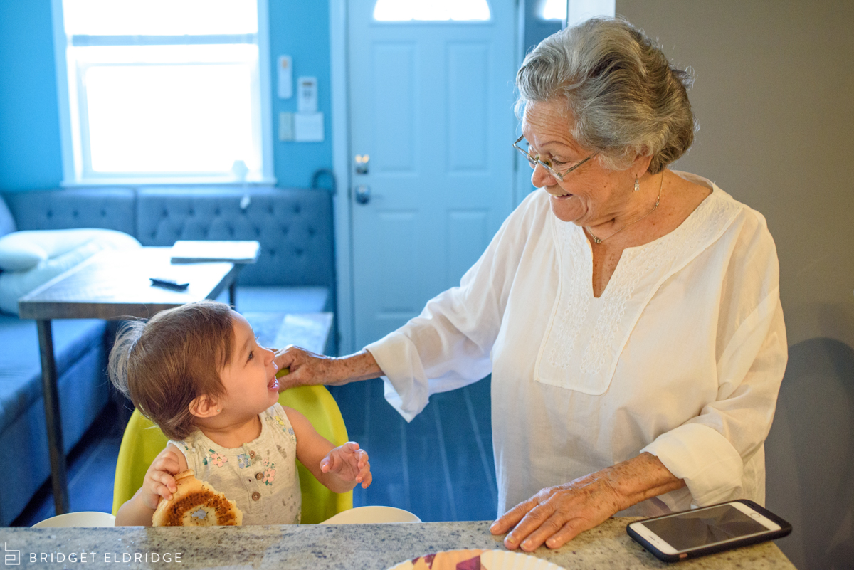 baby smiles at grandma in the kitchen