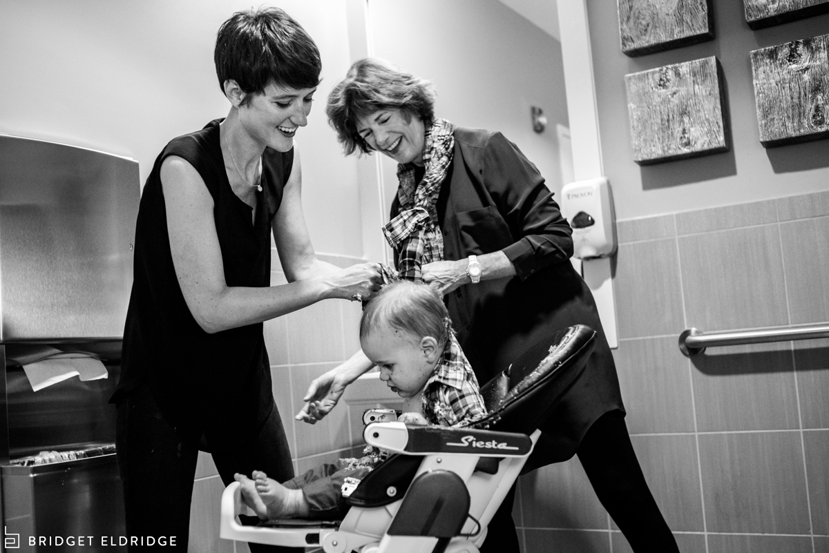 mom and grandma clean up the birthday boy after he is done eating cake