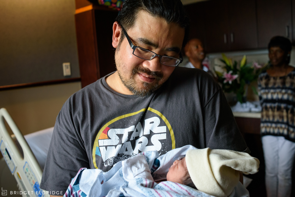 dad looks at his new son in the hospital