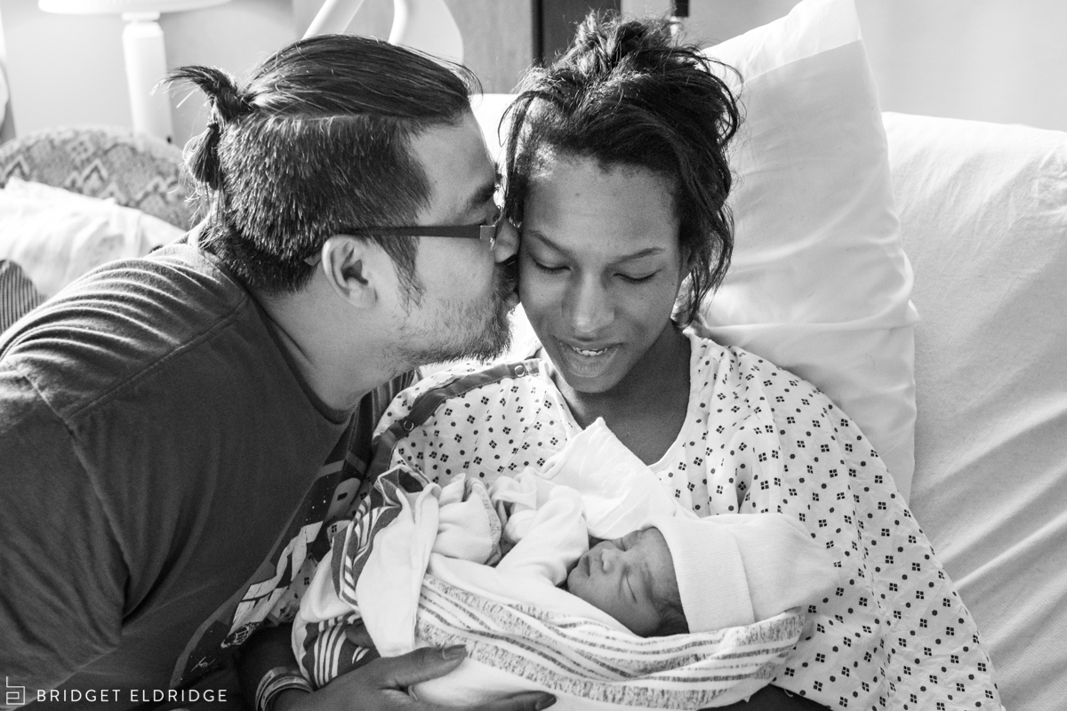 dad kisses mom as she holds her son in the hospital