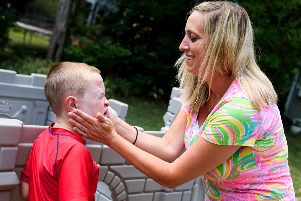 mom slathers sunscreen on her son's face