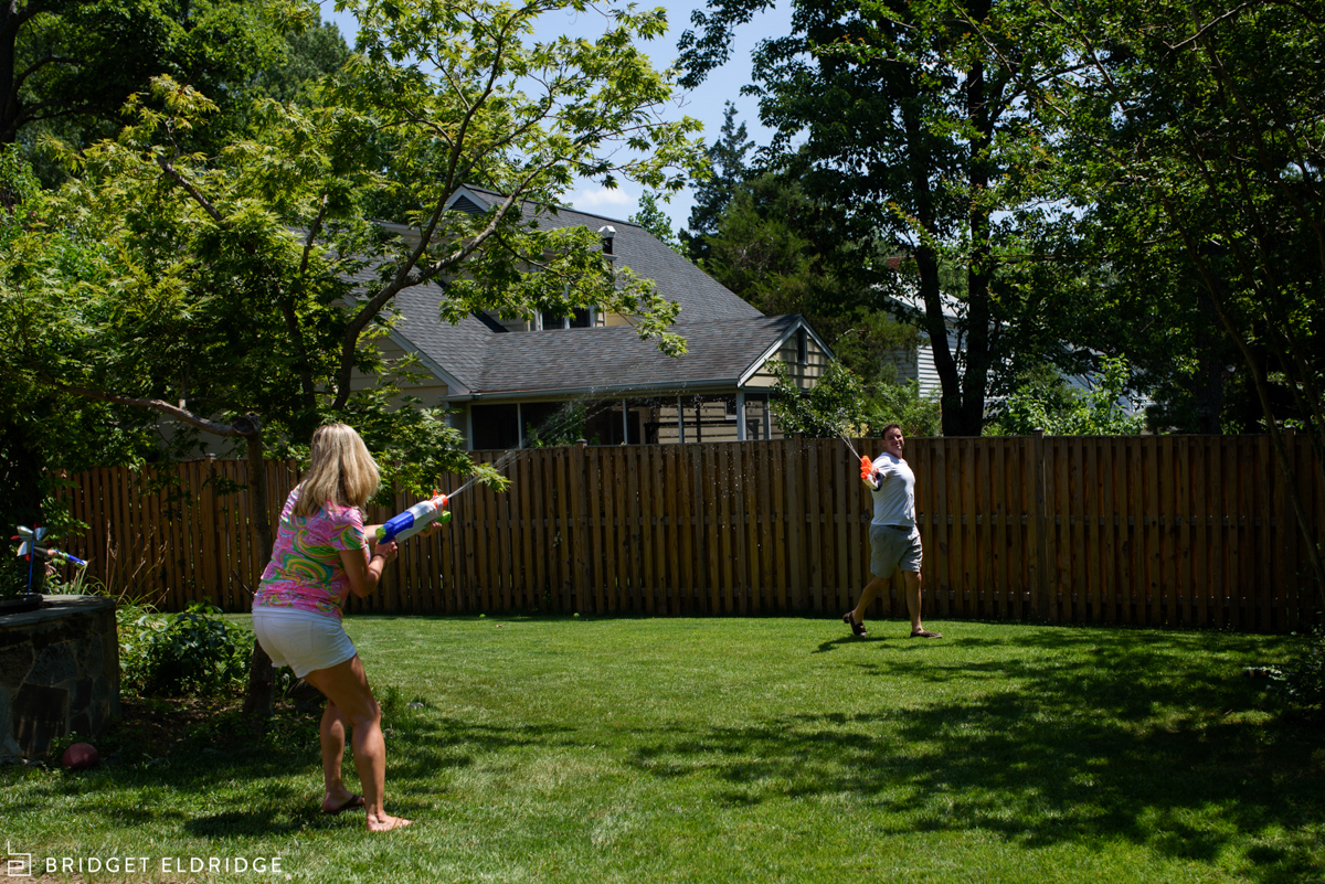 mom chases dad with a water gun