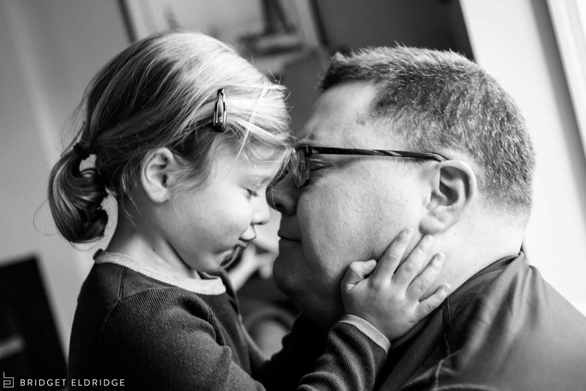 little girl holds her dad's face