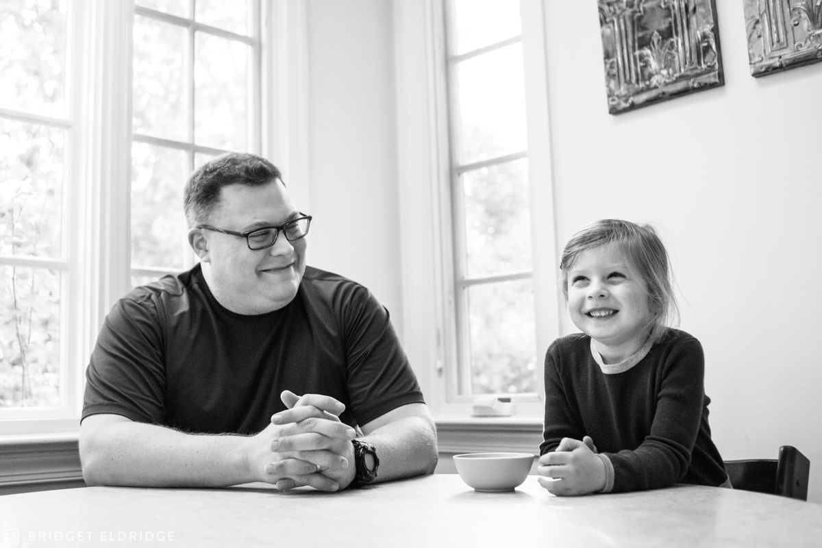 father and daughter sit at the kitchen table