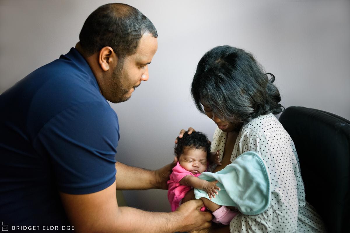mom hands dad their newborn daughter after a feeding