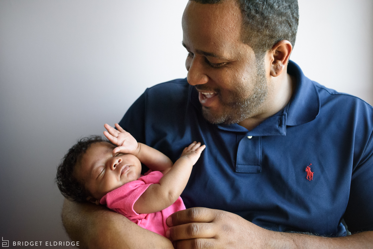 dad smiles at newborn daughter