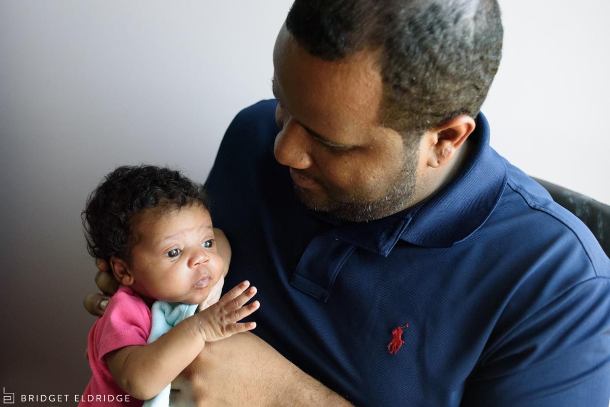 dad takes care of newborn daughter