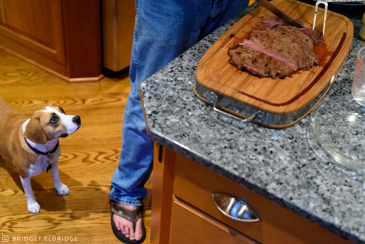 dog watches on as grandfather cuts meat