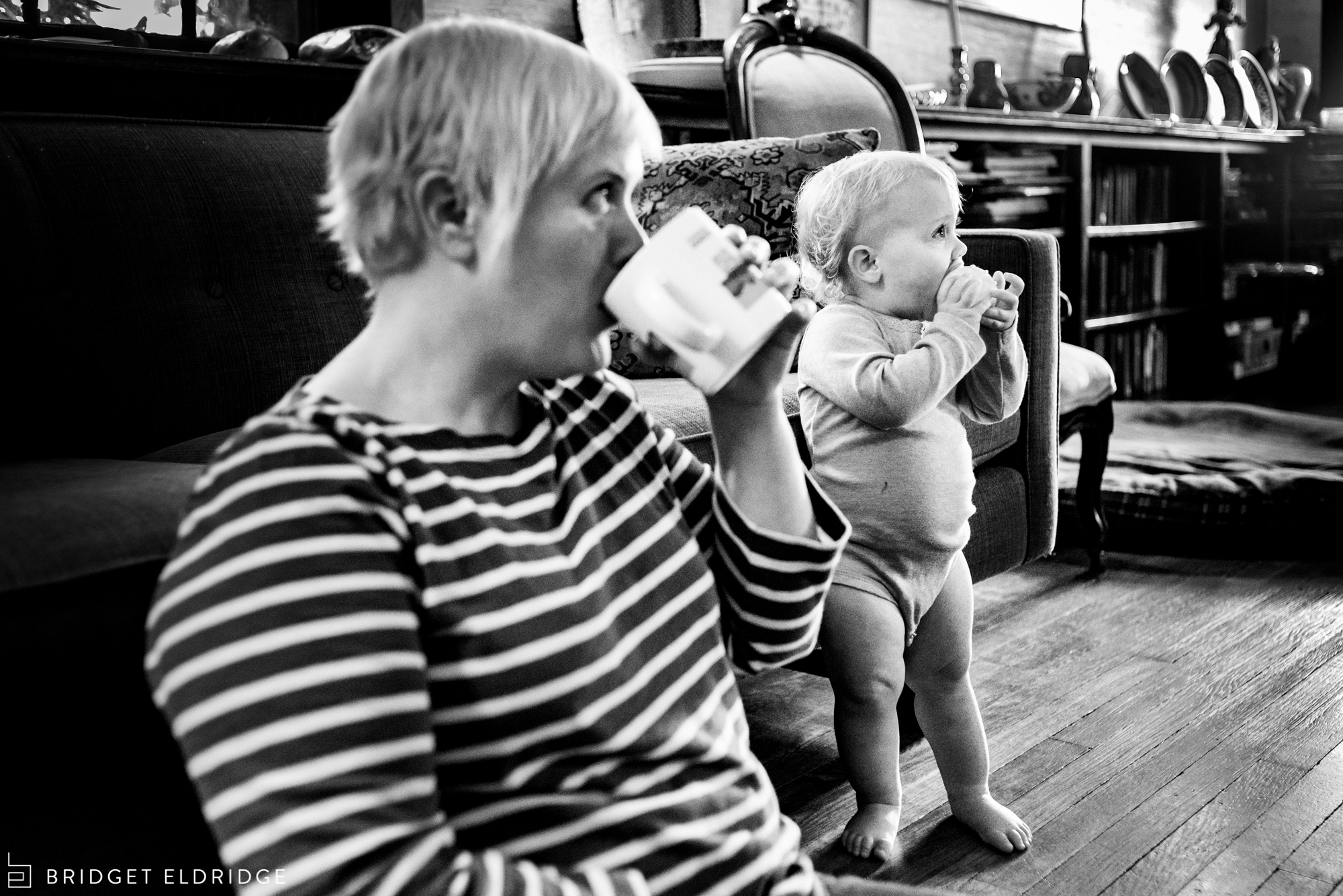 mom and baby mirror each other as they take a sio of a drink