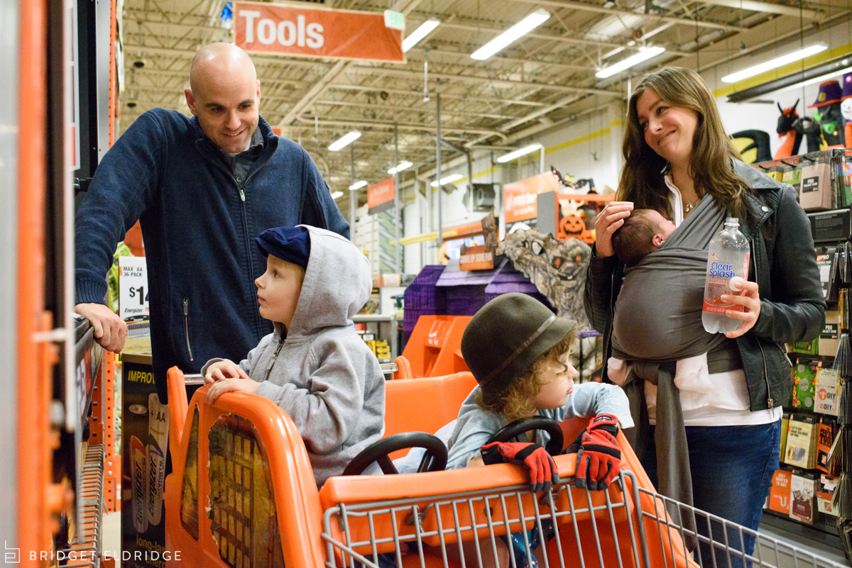 parents watch son look at the drills at home depot