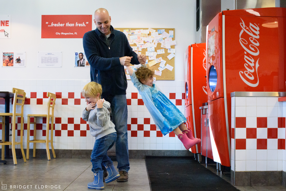 father plays with children at five guys