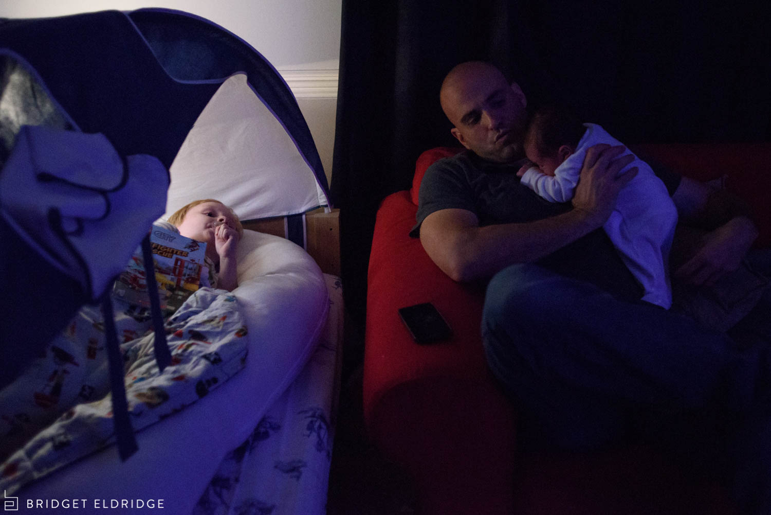 father comforts baby as he puts his oldest son to sleep