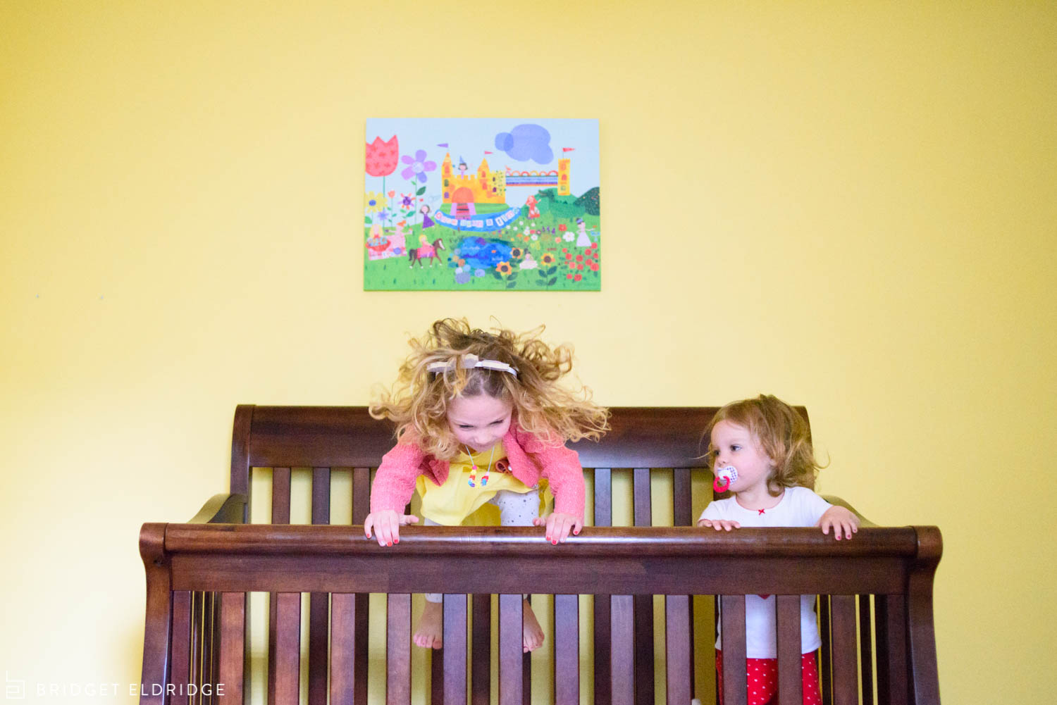 sisters jump in crib together