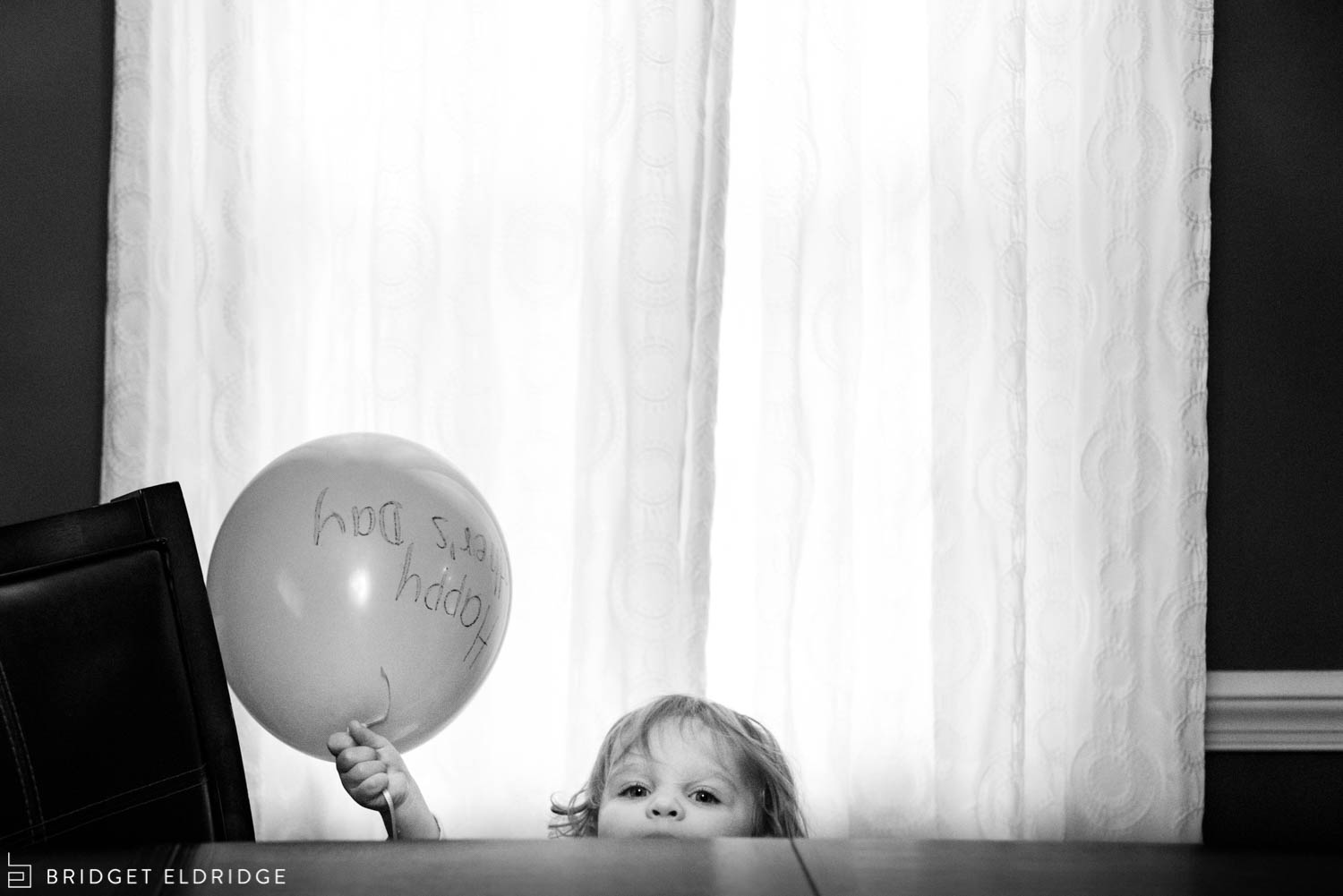 toddler brings the happy mother's day balloon to the breakfast table