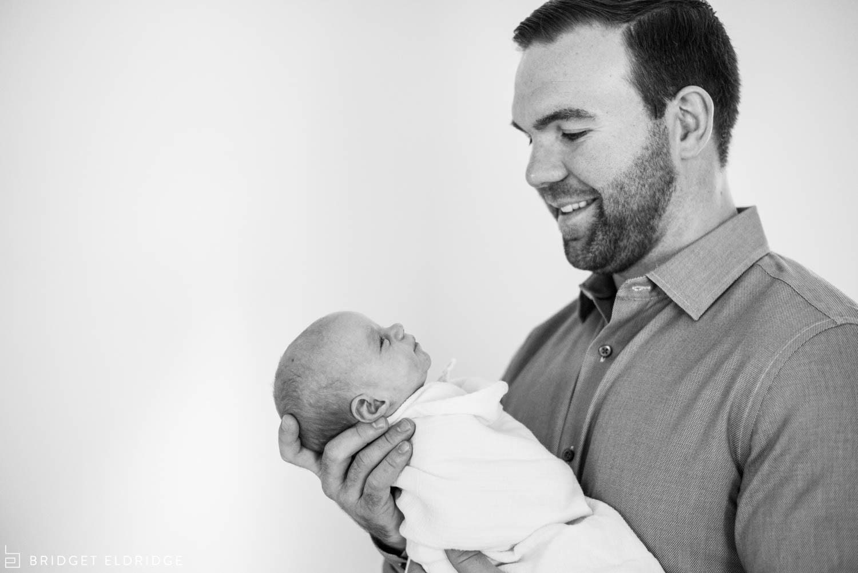 dad looks at his newborn daughter