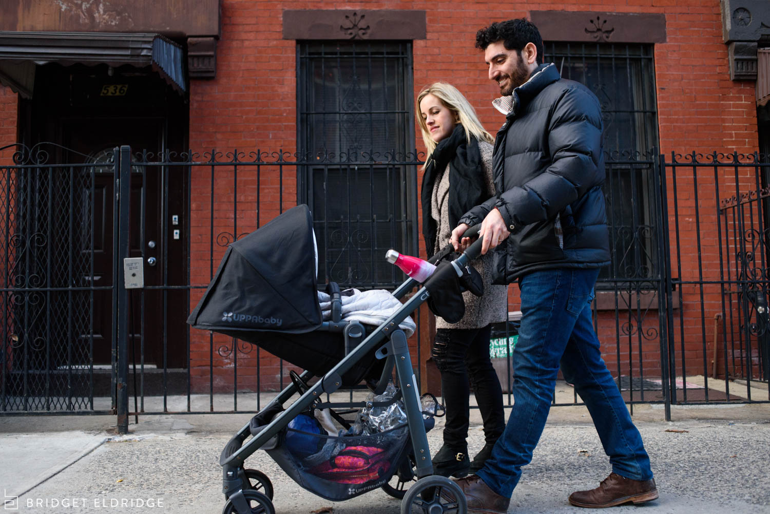 parents walk down the street in brooklyn with newborn baby