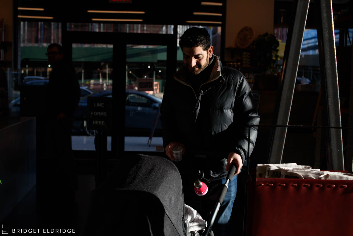 dad pushes the stroller into a coffee shop