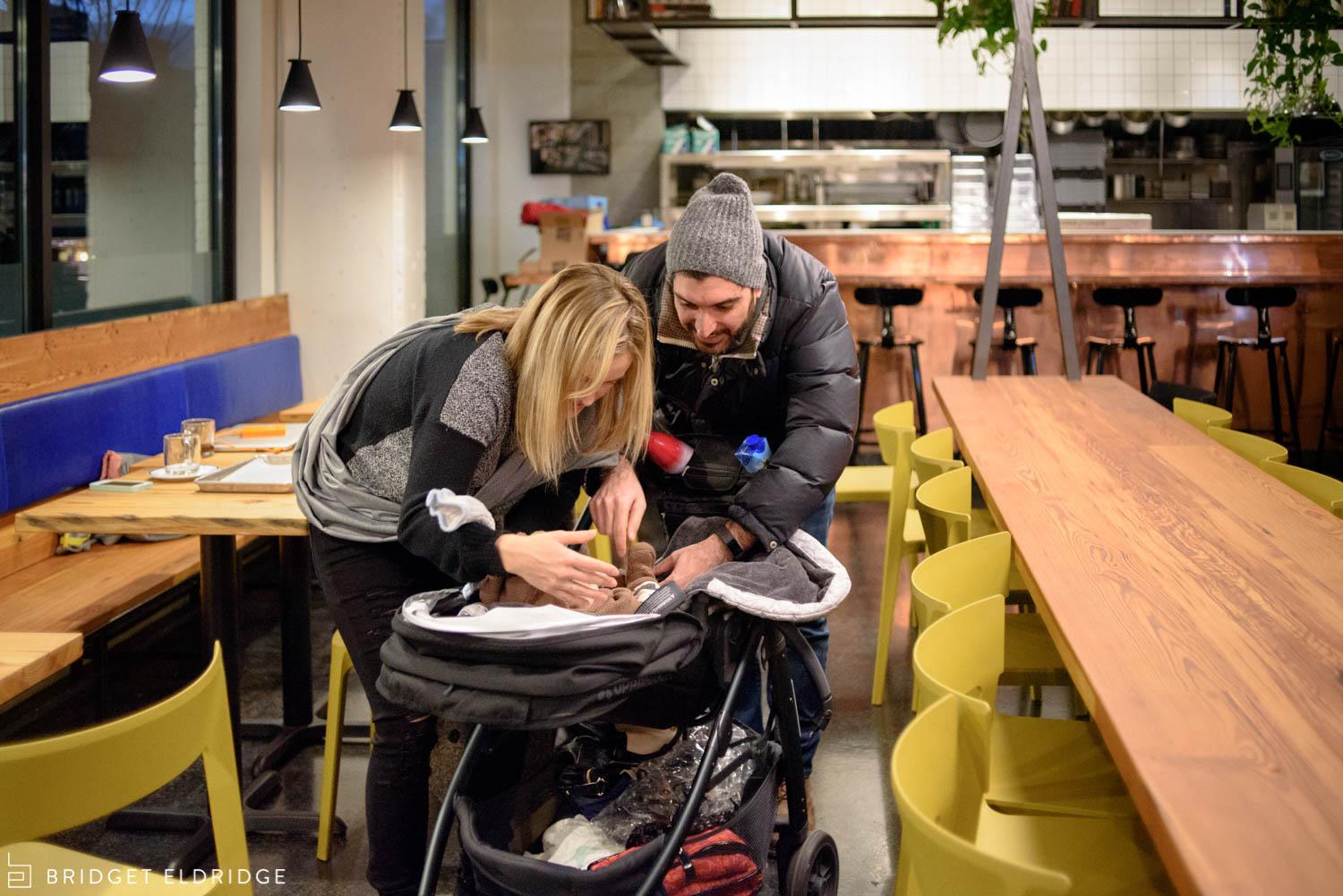 parents strap newborn baby into his stroller