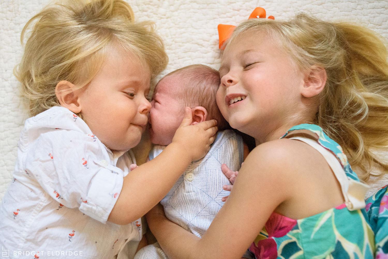 siblings hug new baby