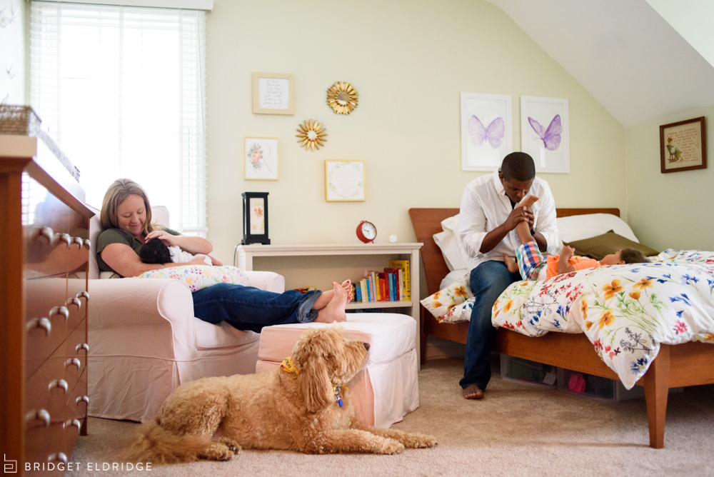 mother rubs baby's forehead while dad smells his son's feet. the family dog looks on.