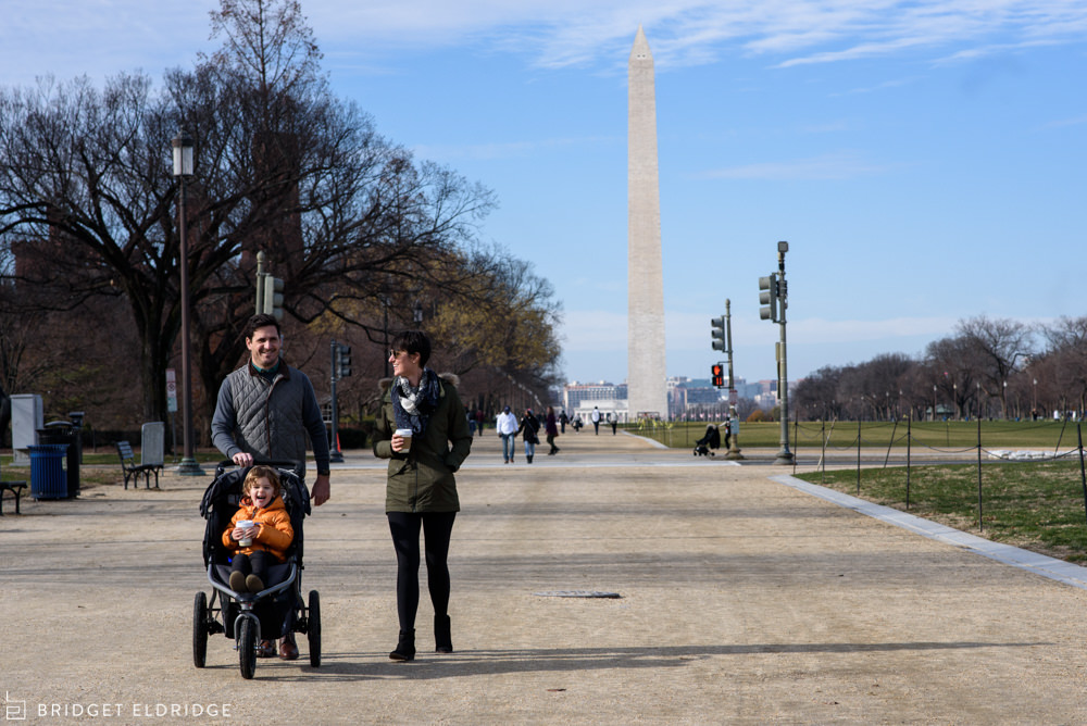 family walks down the national mall with the washington monument in the background