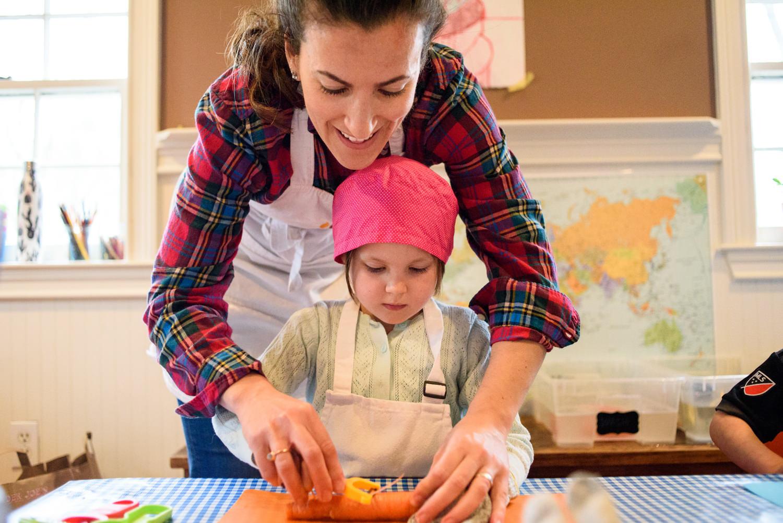 Mari teaches girl how to safely peel a carrot
