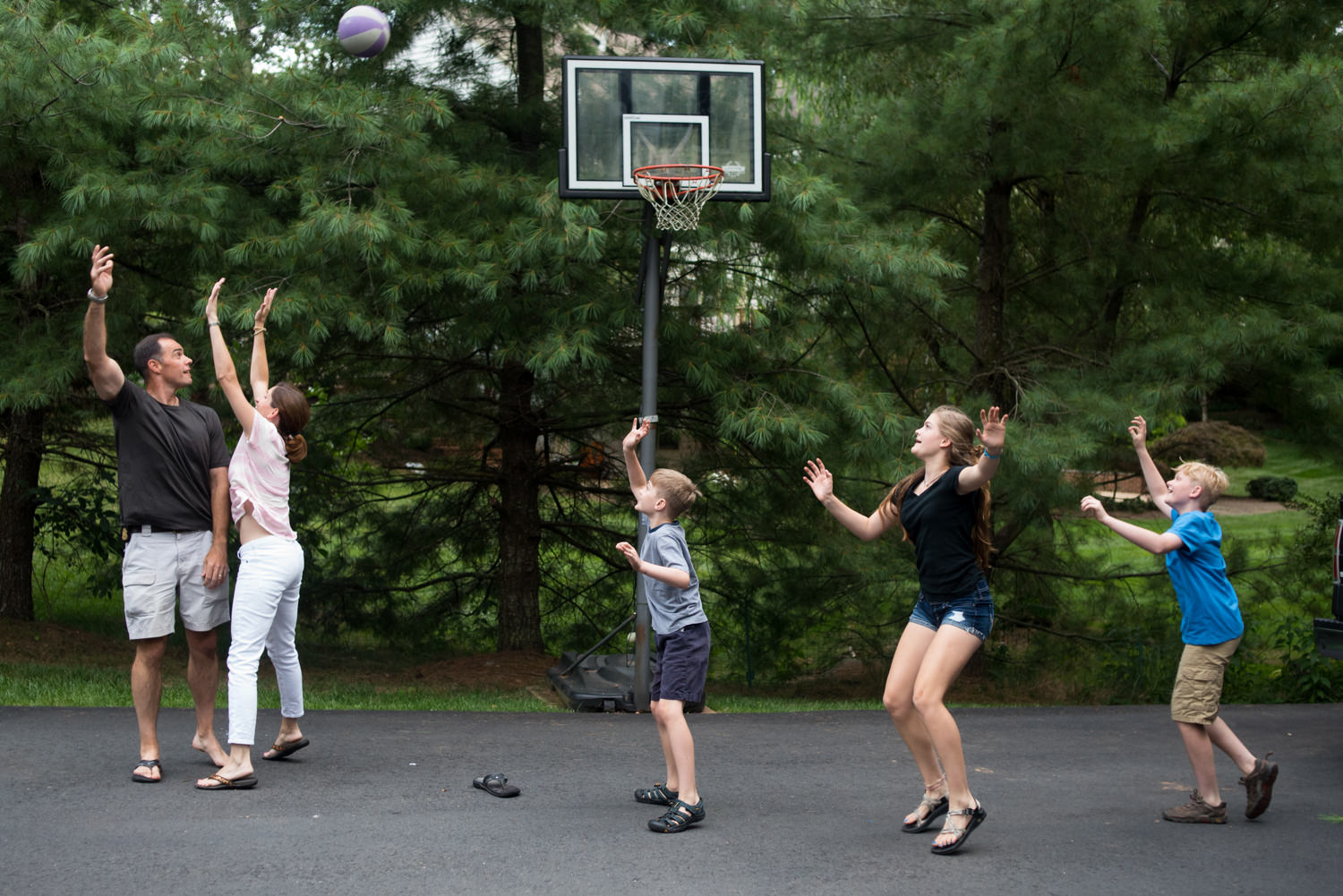 dad throws a basketball while mom blocks him
