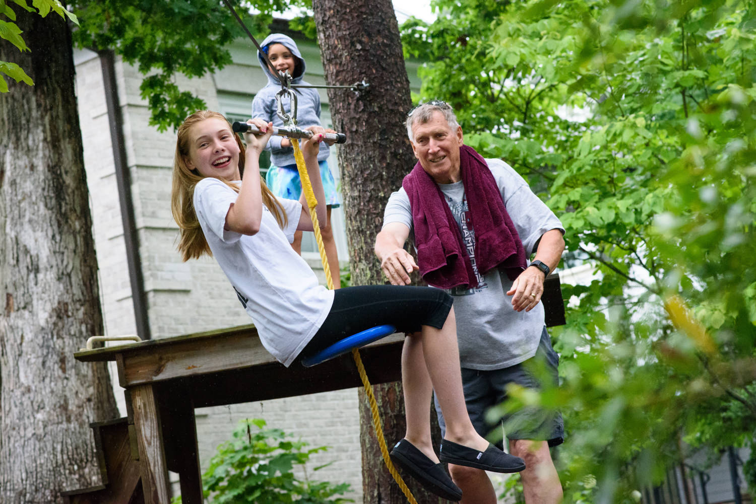 grandfather pushes his granddaughter on a zip line