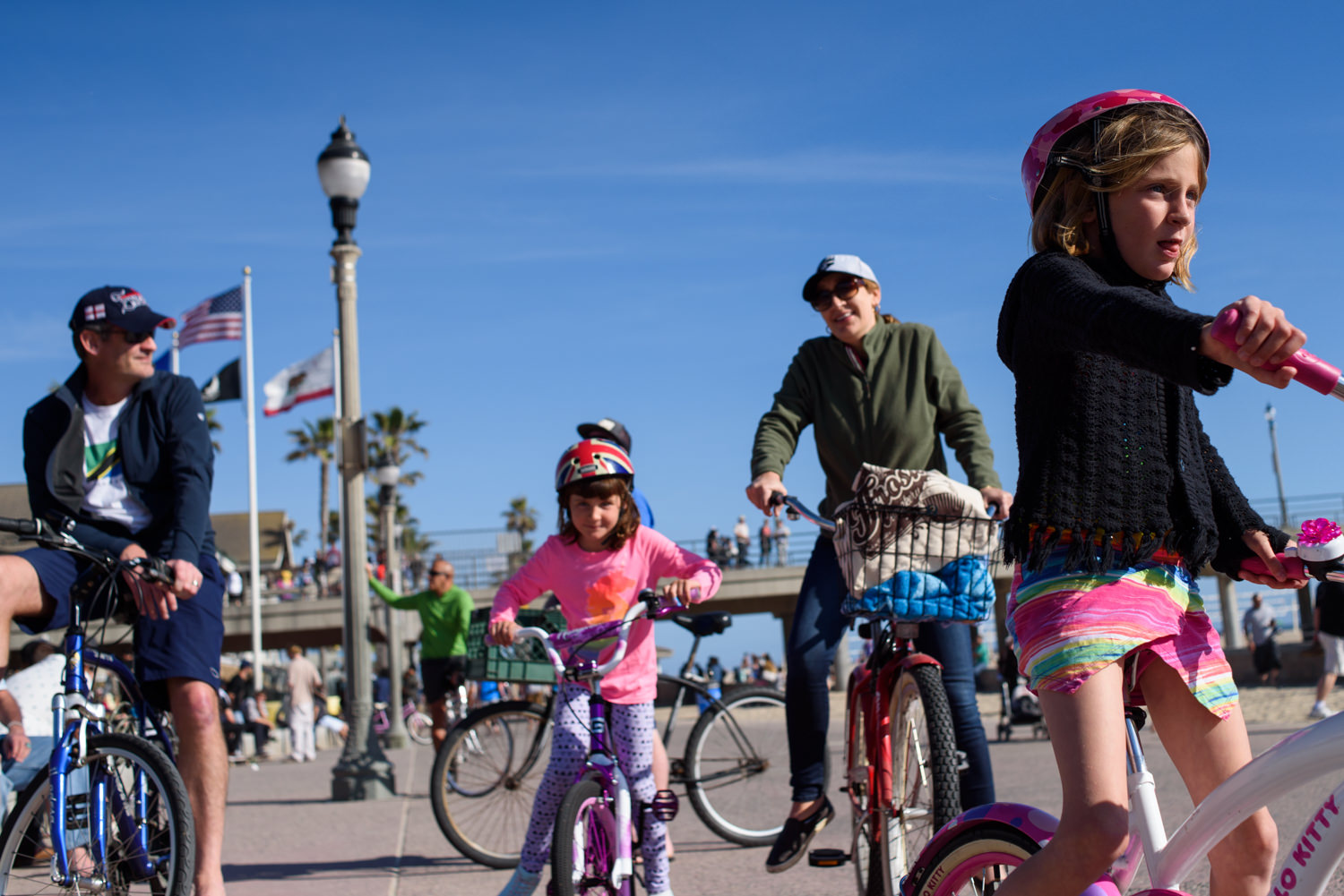 family rides bikes on the boardwalk in huntington beach