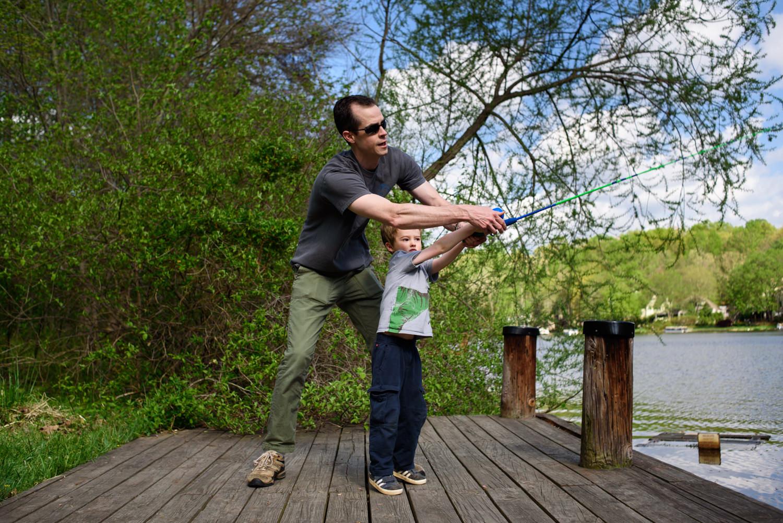 dad helps his son cast a line