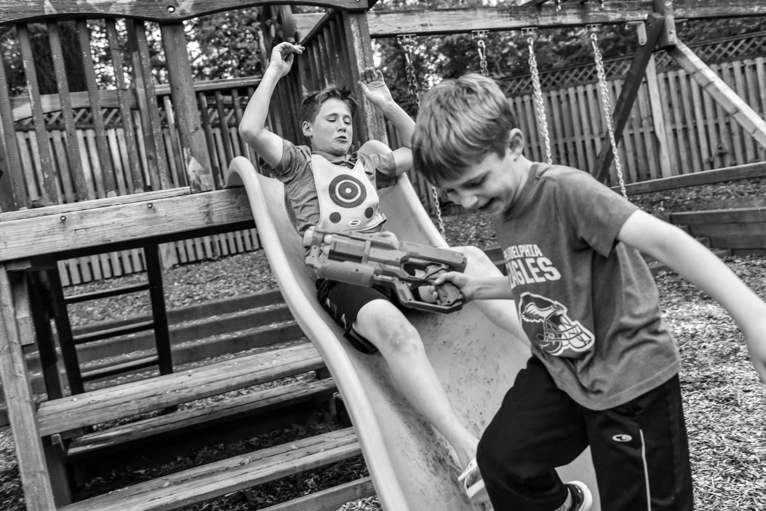boys have a water gun fight on a swing set